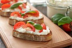 Bruschetta italiano hecho en casa del bocadillo con los tomates, el queso Feta y la albahaca en tabla de cortar Fotos de archivo