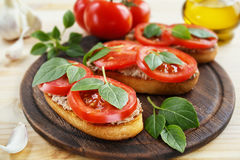 Bruschetta with liver pate, tomatoes and basil. Bruschetta with liver pate, tomatoes and basil on a wooden board. Traditional Italian snack. Close-up Stock Photography