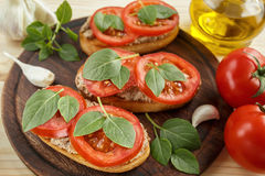 Bruschetta with liver pate, tomatoes and basil. Bruschetta with liver pate, tomatoes and basil on a wooden board. Traditional Italian snack. Close-up Royalty Free Stock Photos