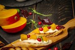 Bruschetta med den s?ta mango, granat?pple, ost P? tr?bakgrund Sund mat, plan b?sta sikt royaltyfria bilder
