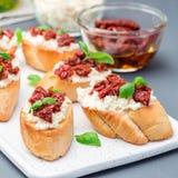 Bruschetta med den sol torkad tomaten, feta och philadelphia ost och basilika på den keramiska plattan, fyrkantigt format arkivfoton