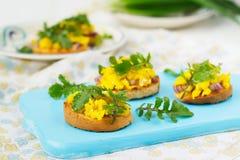 Bruschetta med förvanskad ägg och arugula Fotografering för Bildbyråer