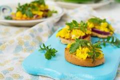 Bruschetta med förvanskad ägg och arugula Arkivfoton