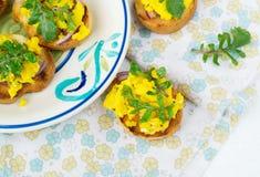 Bruschetta med förvanskad ägg och arugula Arkivfoto