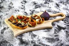 Bruschetta med fikonträd med ost, honung Italiensk aptitretare Lekmanna- lägenhet Top beskådar banta förlustvikt för begrepp royaltyfri foto