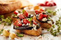 Bruschetta med grillad aubergine, körsbärsröda tomater, fetaost, kapris och nya aromatiska örter på en trätabell Läckra Medit Arkivbild