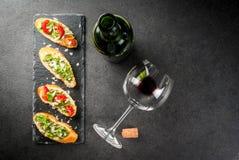 Bruschetta med pesto, parmesan, tomater och basilika Arkivfoto