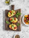 Bruschetta med tomater och avokadot på lantlig träskärbräda läckert mellanmål arkivbild