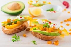Bruschetta met avocado, gele peper, korrels van graan, peterselie en Spaanse peperpeper op een lichte houten achtergrond Royalty-vrije Stock Foto