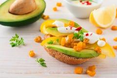 Bruschetta met avocado, gele peper, korrels van graan, peterselie en Spaanse peperpeper op een lichte houten achtergrond Royalty-vrije Stock Afbeeldingen