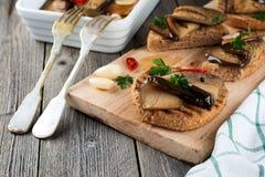 Bruschetta met gemarineerde aubergine met Spaanse pepers, knoflook en peterselie op een houten tribune Stock Foto's