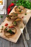 Bruschetta met gemarineerde aubergine met Spaanse pepers, knoflook en peterselie op een houten tribune Stock Afbeeldingen
