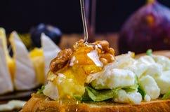 Bruschetta met kaas, fruit en noten wordt gemotregend met honing stock afbeeldingen