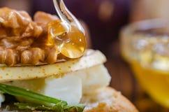 Bruschetta met kaas, fruit en noten wordt gemotregend met honing stock foto