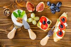 bruschetta met kaas, fruit en noten wordt gemotregend met honing, op een houten lijst stock afbeeldingen