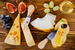 bruschetta met kaas, fruit en noten wordt gemotregend met honing, op een houten lijst stock fotografie