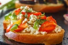 Bruschetta met rode paprika en geitkaas op een zwarte lijst aangaande een achtergrond van verse groenten Royalty-vrije Stock Foto
