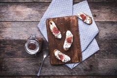 Bruschetta met roomkaas en fig. op hakbord in rusti Stock Afbeeldingen