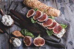 Bruschetta met roomkaasfig. en spinazie verlaat, op een houten oppervlakte, rustieke stijl royalty-vrije stock afbeelding