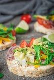 Bruschetta met tomaat, avocado, kruiden en arugula Rustieke achtergrond Hoogste mening stock afbeelding