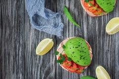 Bruschetta met tomaat, avocado, kruiden en arugula Rustieke achtergrond Hoogste mening stock afbeeldingen