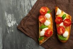 Bruschetta met tomaten, mozarellakaas en basilicum in een witte plaat Traditionele Italiaanse snack of snack, antipasto Met ruimt royalty-vrije stock afbeelding