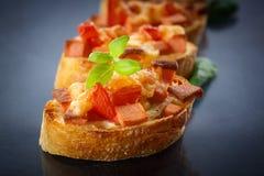 Bruschetta mit Käse und Tomaten Stockbilder
