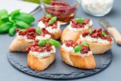 Bruschetta mit sonnengetrockneter Tomate, Feta und Philadelphia-Käse und -basilikum auf der Steinplatte, horizontal lizenzfreies stockbild