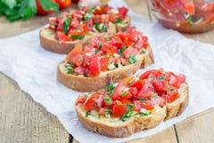 Bruschetta mit Tomaten, Kräutern und Öl auf Knoblauchkäsebrot lizenzfreies stockbild