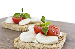 Bruschetta with mozarella and tomatoes. Wood background Royalty Free Stock Image