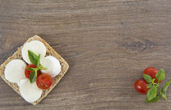 Bruschetta with mozarella and tomatoes. On wood background Royalty Free Stock Images