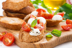 Bruschetta with mozzarella, basil and cherry tomatoes on wood Royalty Free Stock Photography