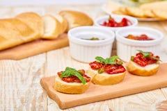 Bruschetta o crostini con i pomodori ed i capperi seccati al sole fotografia stock libera da diritti