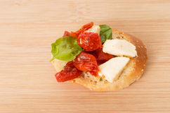Bruschetta with olive oil, sundried tomatoes. Mozarella and fresh basil  on  wooden board Stock Photos