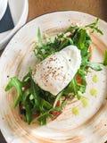Bruschetta op een plaat in een koffie met arugulatomaten en gestroopt ei stock afbeelding