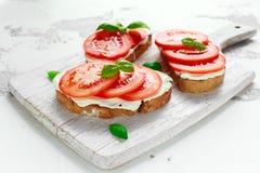 Bruschetta, pane tostato con formaggio a pasta molle, basilico e pomodori su un bordo di legno bianco Spuntino sano italiano, ali fotografia stock libera da diritti