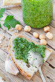 Bruschetta With Parsley Pesto. Closeup of bruschetta with fresh made parsley pesto besides  some ingredients necessary for its preparation: parsley, hazelnuts Royalty Free Stock Photos
