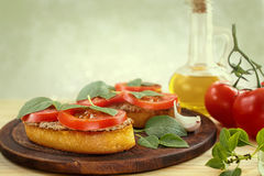 Bruschetta with pate, tomatoes and basil. Bruschetta with liver pate, tomatoes and basil on a wooden board. Traditional Italian snack. Close-up stock photography