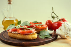 Bruschetta with pate, tomatoes and basil. Bruschetta with liver pate, tomatoes and basil on a wooden board. Traditional Italian snack. Close-up royalty free stock image