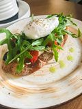 Bruschetta on a plate in a cafe with arugula tomatoes and poached egg stock photography