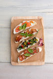 Bruschetta platter: salmon, olives, bacon. Bruschetta platter: salmon, olives, tomatoes, bacon, garlic, basil and onion on a wooden board on a white table, close Stock Image