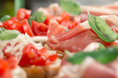 Bruschetta with prosciutto, tomatoes, fresh basil close up Royalty Free Stock Image