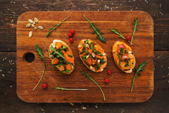 Bruschetta with pumpkin on board flat lay. Top view on catering platter with three vegetarian toasts with squash and seasonal. Vegetable meal, healthy food Royalty Free Stock Photo
