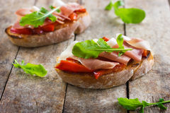 Bruschetta with roasted peppers, prosciutto and arugula. On rustic backgroundn stock photo