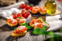 Bruschetta sabroso con el tomate, albahaca, parmesano, aceite de oliva imagen de archivo