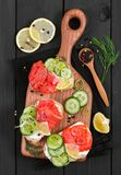 Bruschetta with salmon and fresh cucumber on cutting board. On black wooden background. Top view Royalty Free Stock Photo