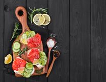 Bruschetta with salmon and fresh cucumber on cutting board. On black wooden background. Top view Stock Photography