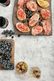 Bruschetta, sandwich with Italian ham, grapes, olives with red Stock Image