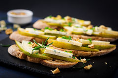 Bruschetta sandwich with pear, blue cheese, honey and nut. On a dark background Stock Image