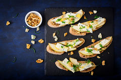 Bruschetta sandwich with pear, blue cheese, honey and nut. On a dark background. Flat lay. Top view Royalty Free Stock Photography